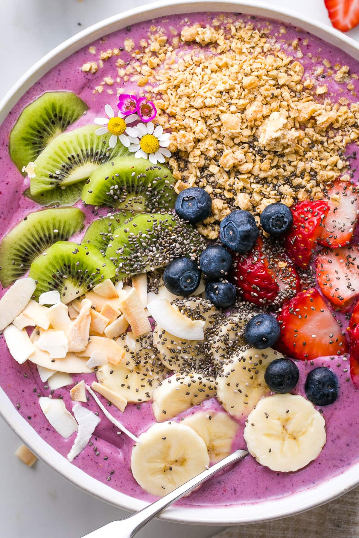 top down view of healthy smoothie bowl with variety of toppings.