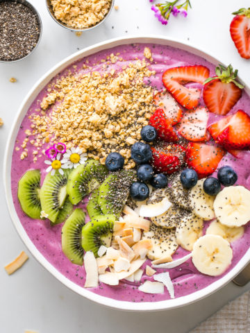 top down view of healthy smoothie bowl with variety of toppings and items surrounding.