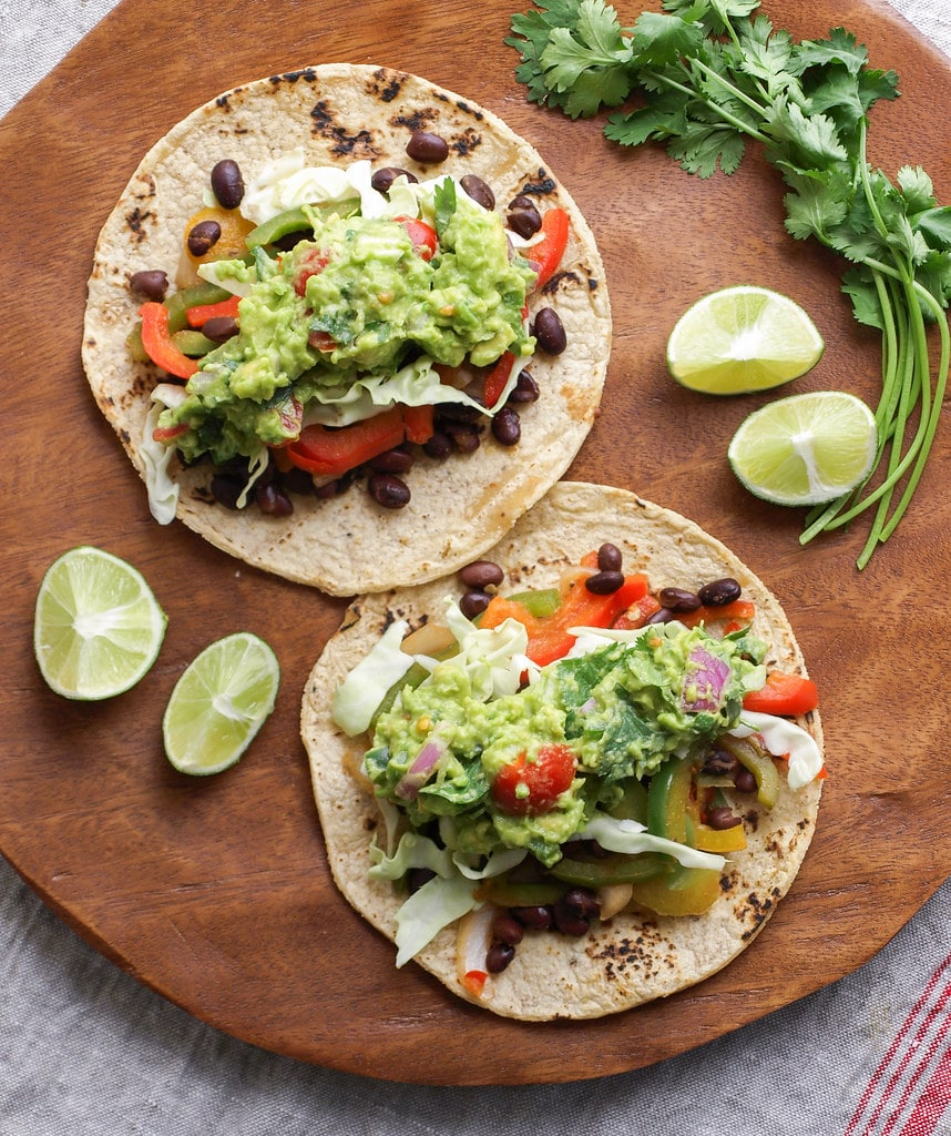top down view of healthy black bean fajitas with guacamole on a wooden plate.
