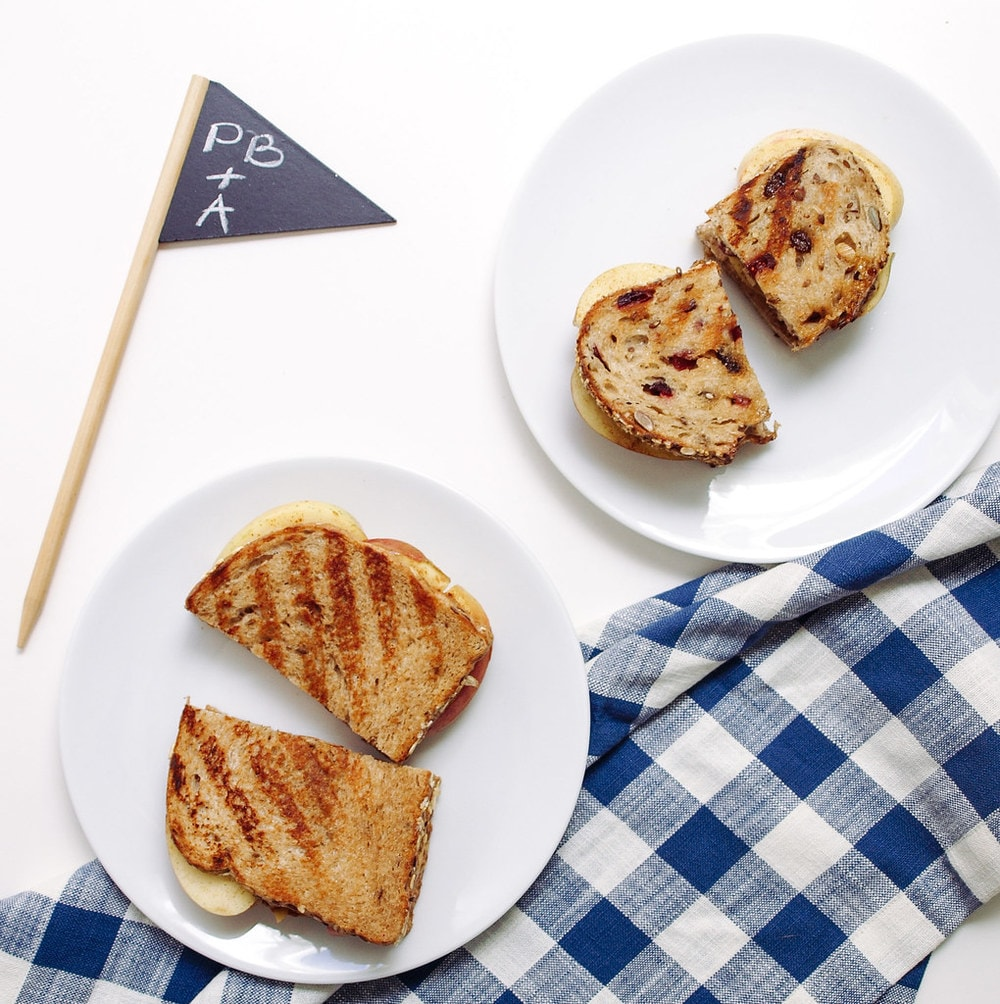 two grilled peanut butter and apple sandwiches on a small white plates with checkered blue and white napkin