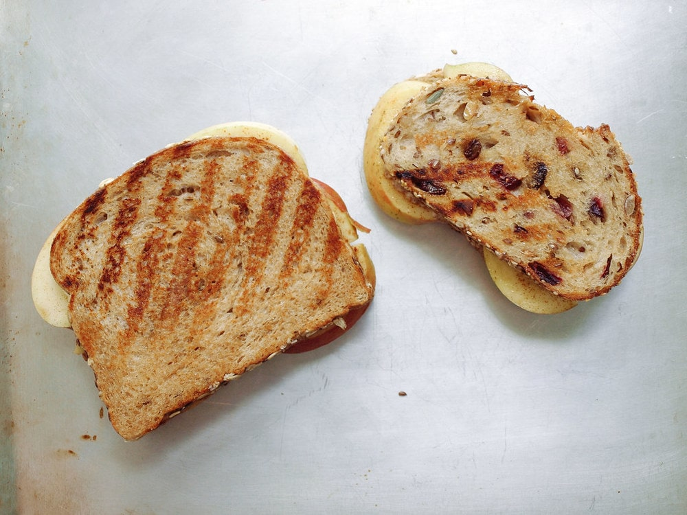two grilled peanut butter and apple sandwiches on a cookie sheet