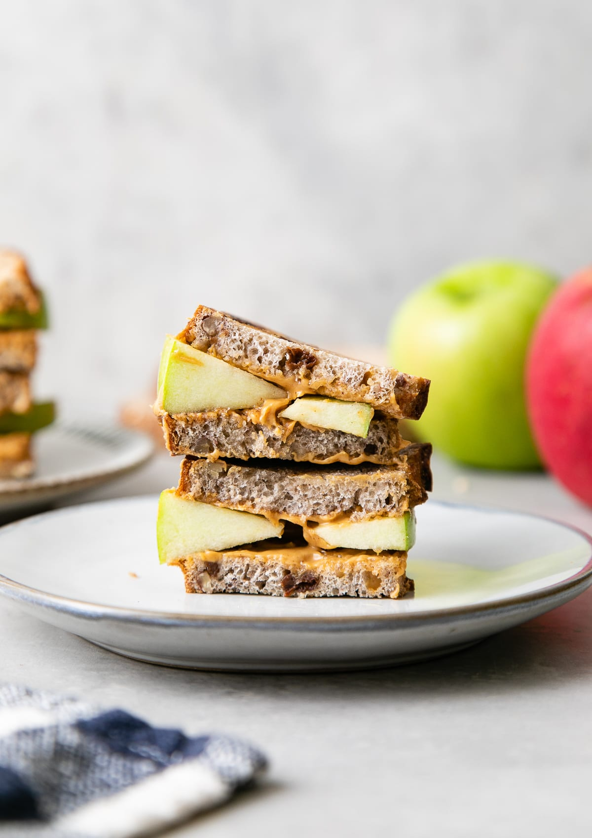 head on view of grilled peanut butter apple sandwich on a plate with items surrounding.