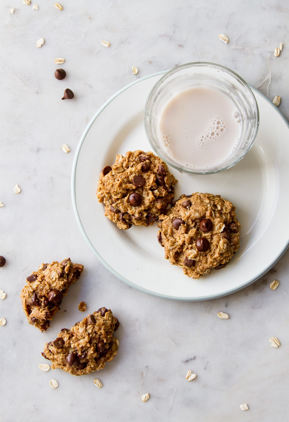 top down view of the healthy vegan oatmeal chocolate chip cookies on a plate with glass of almond milk.