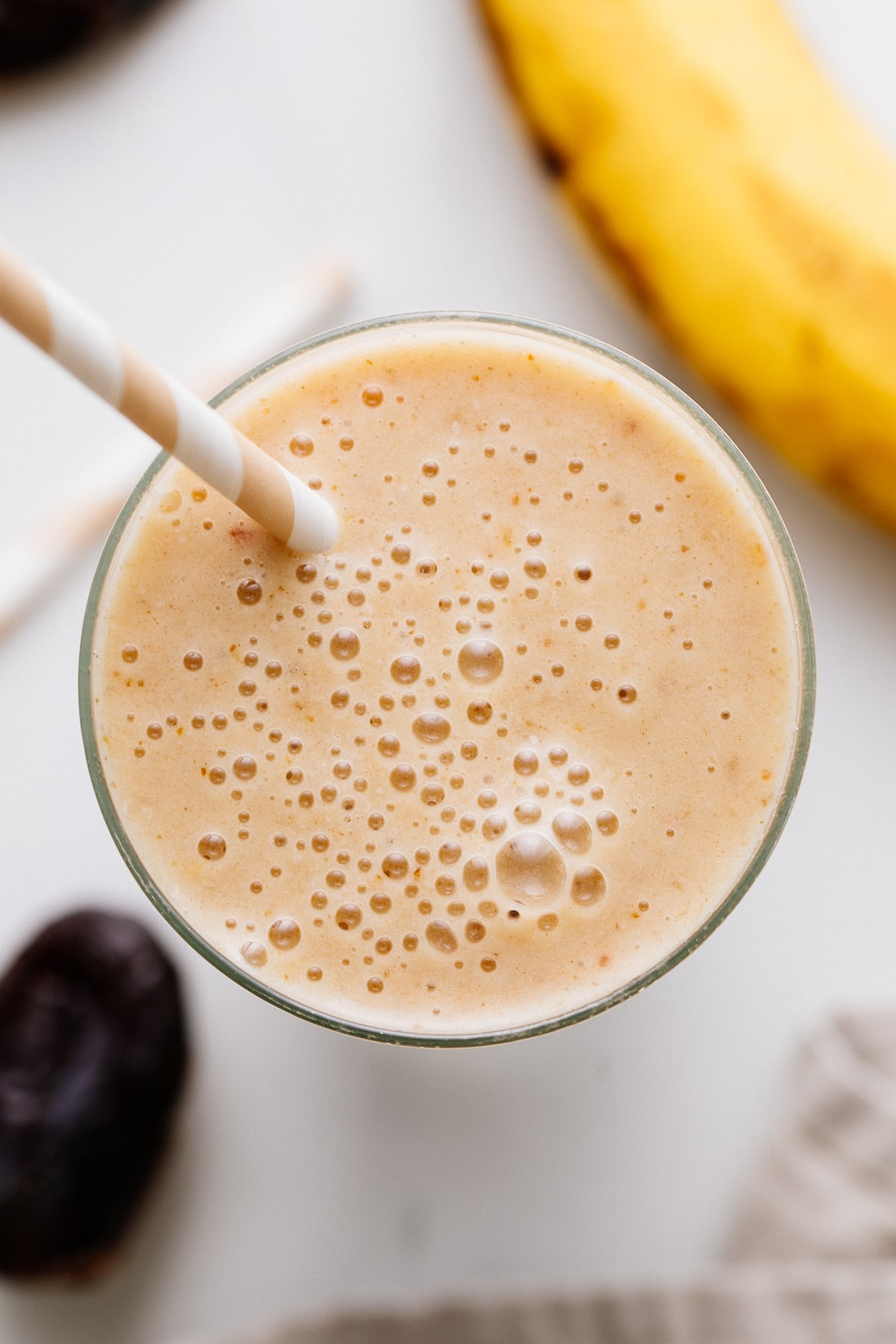 top down view of healthy vanilla date smoothie in a glass with items surrounding.