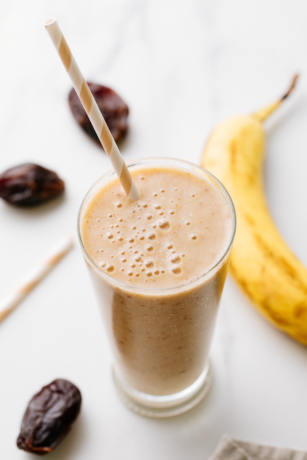 side angle view of healthy vanilla date smoothie in a glass with items surrounding.