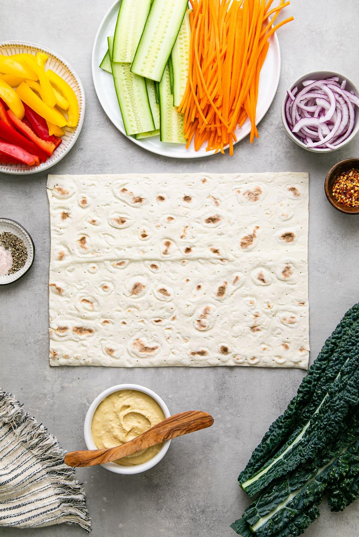 top down view of ingredients needed to make the best hummus veggie wrap.