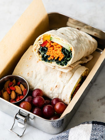 top down view of metal bento box with hummus veggie wrap and other items.
