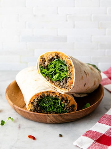 side angle view of two halves of a lentil and sun-dried tomato hummus wrap on a small wooden bowl.
