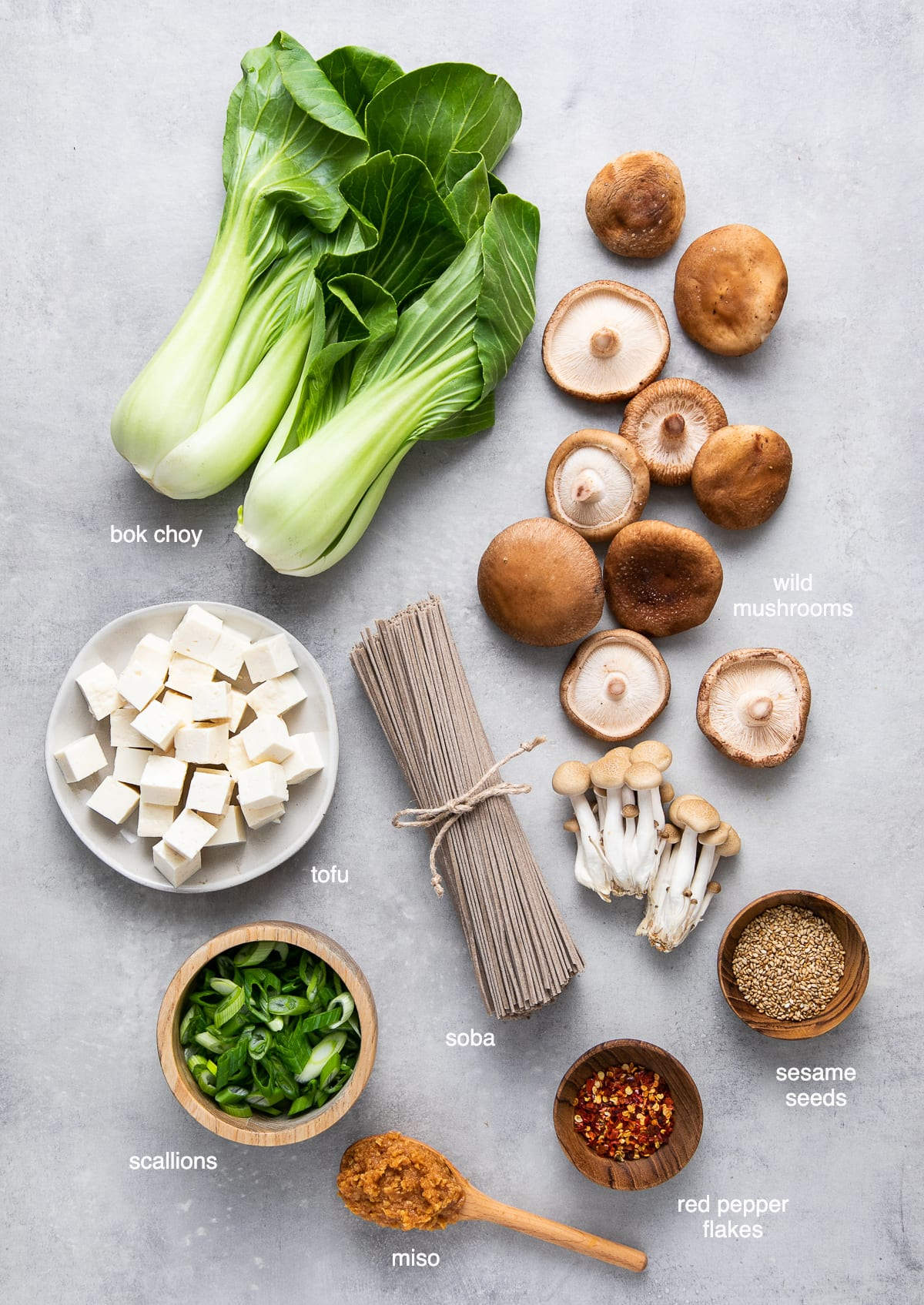 top down view of ingredients needed to make bok choy mushroom miso soba noodle soup
