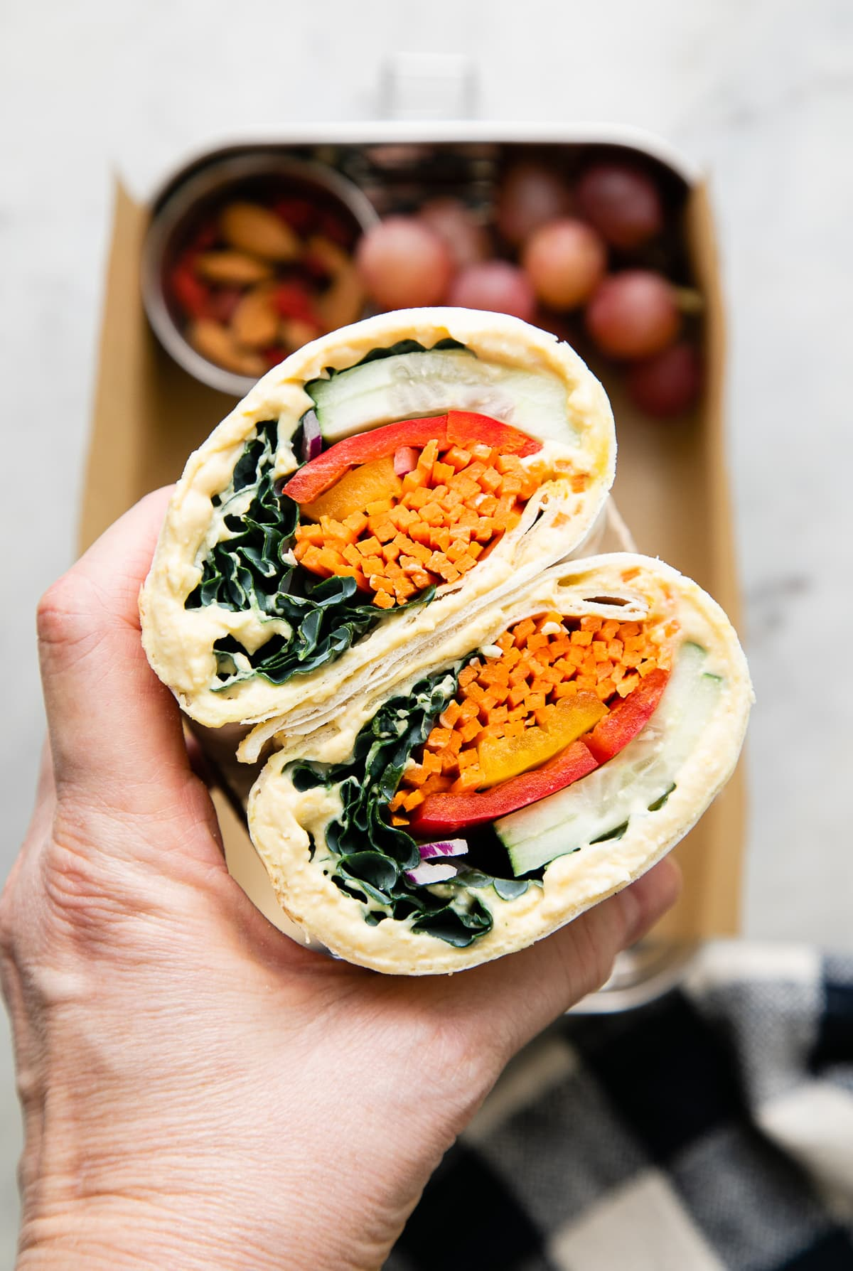 top down view of hand holding a hummus veggie wrap sliced in half.