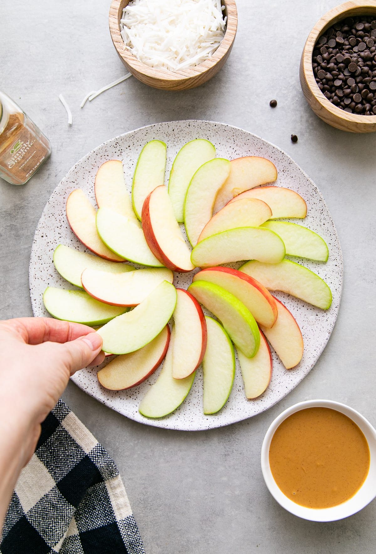 top down view showing the process of layering apples on plate with items surrounding.