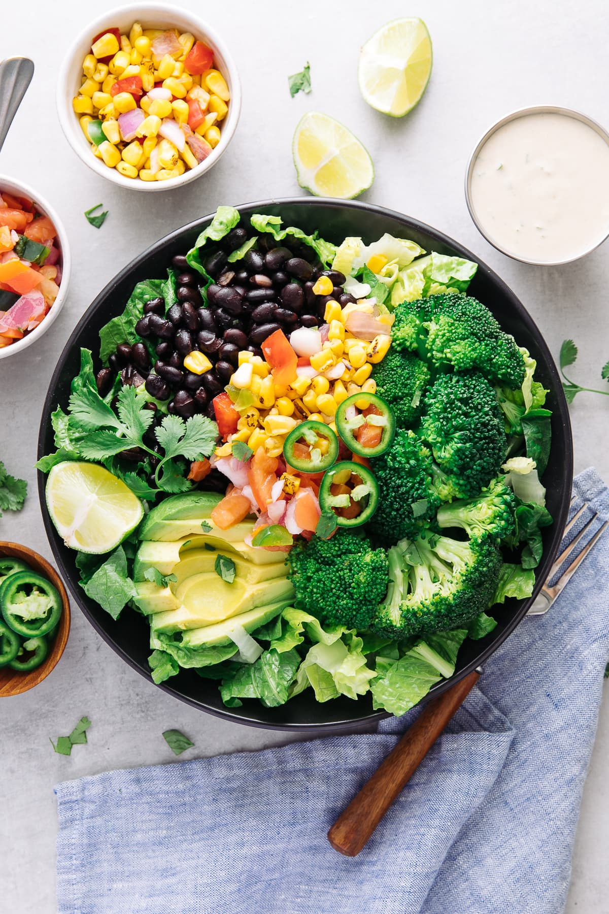 top down view of black bean broccoli salad with avocado in a black bowl with items surrounding.