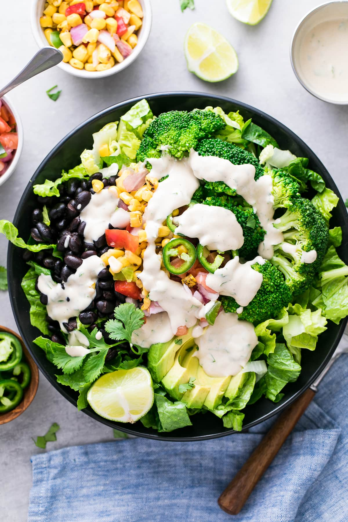 top down view of black bean broccoli salad with avocado and cumin tahini dressing in a black bowl with items surrounding.
