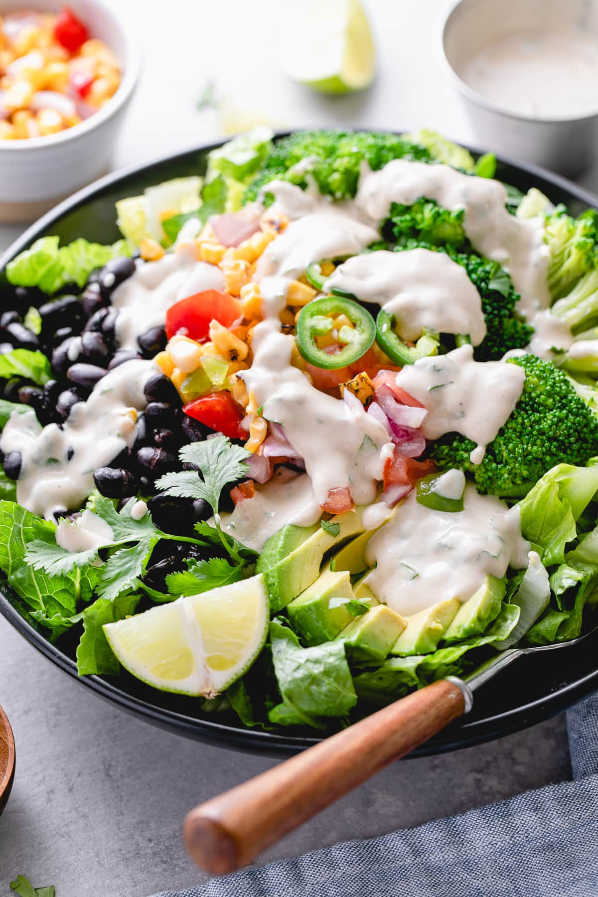 side angle view of black bean broccoli salad with avocado and cumin tahini dressing in a black bowl with items surrounding.