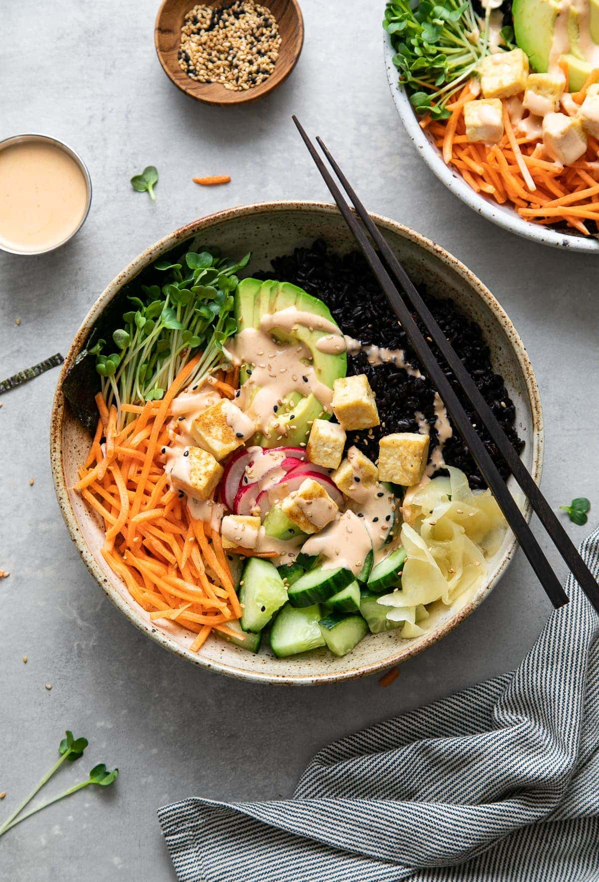 top down view of vegan sushi bowl topped with creamy dynamite sauce with items surrounding.