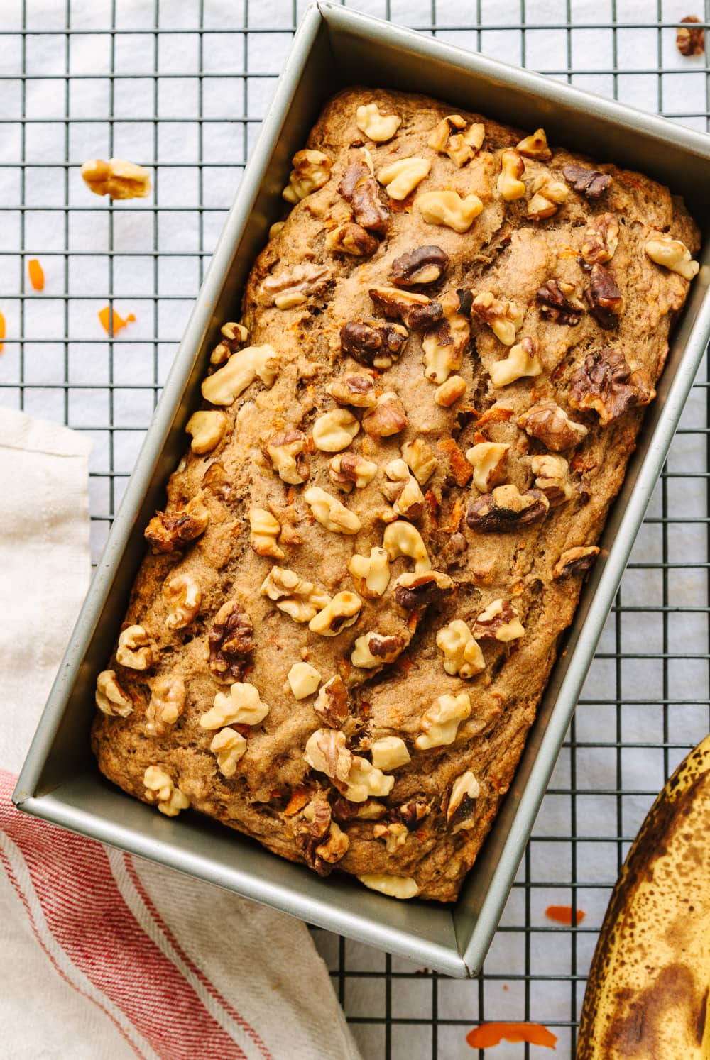 top down view of vegan carrot banana bread in a loaf pan cooling on a wire rack.