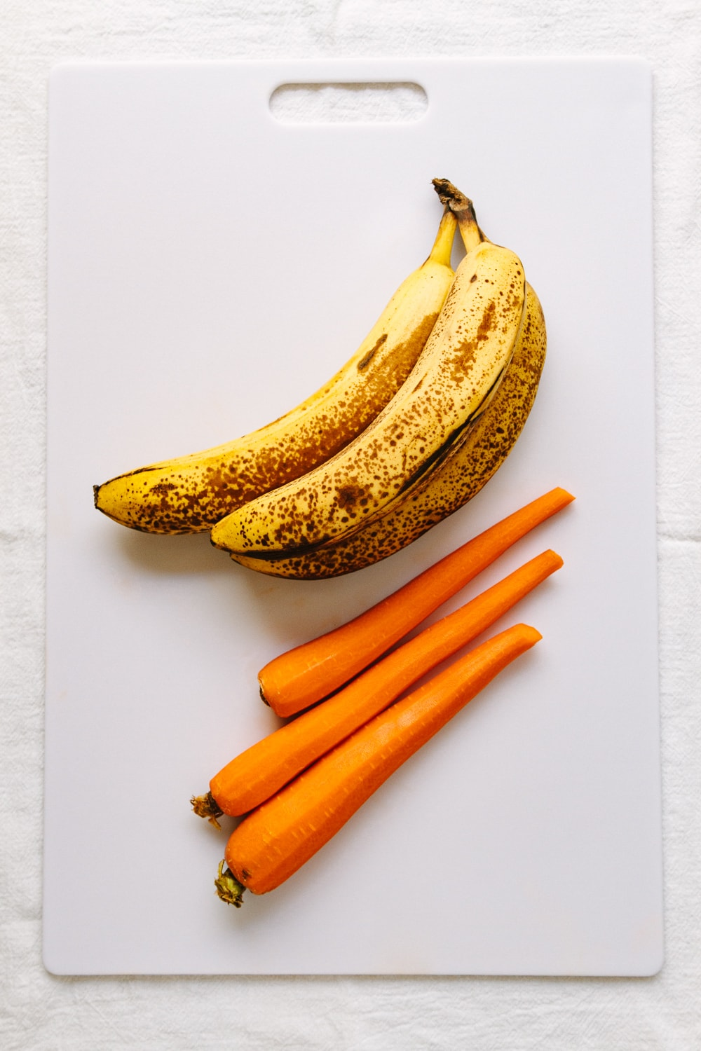 top down view of carrots and bananas on a white cutting board.