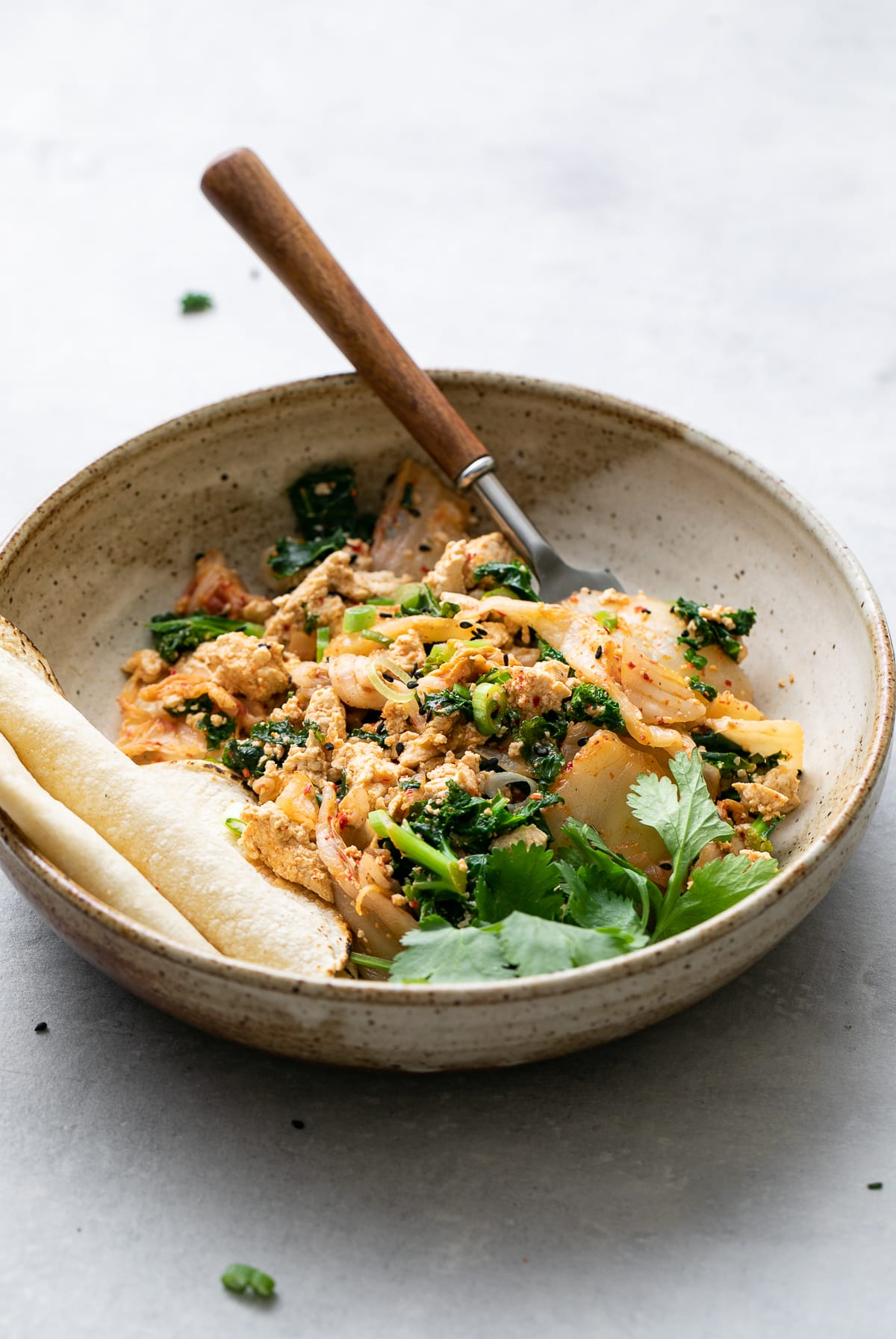 side angle view of bowl with serving of kimchi tofu scramble with fork.
