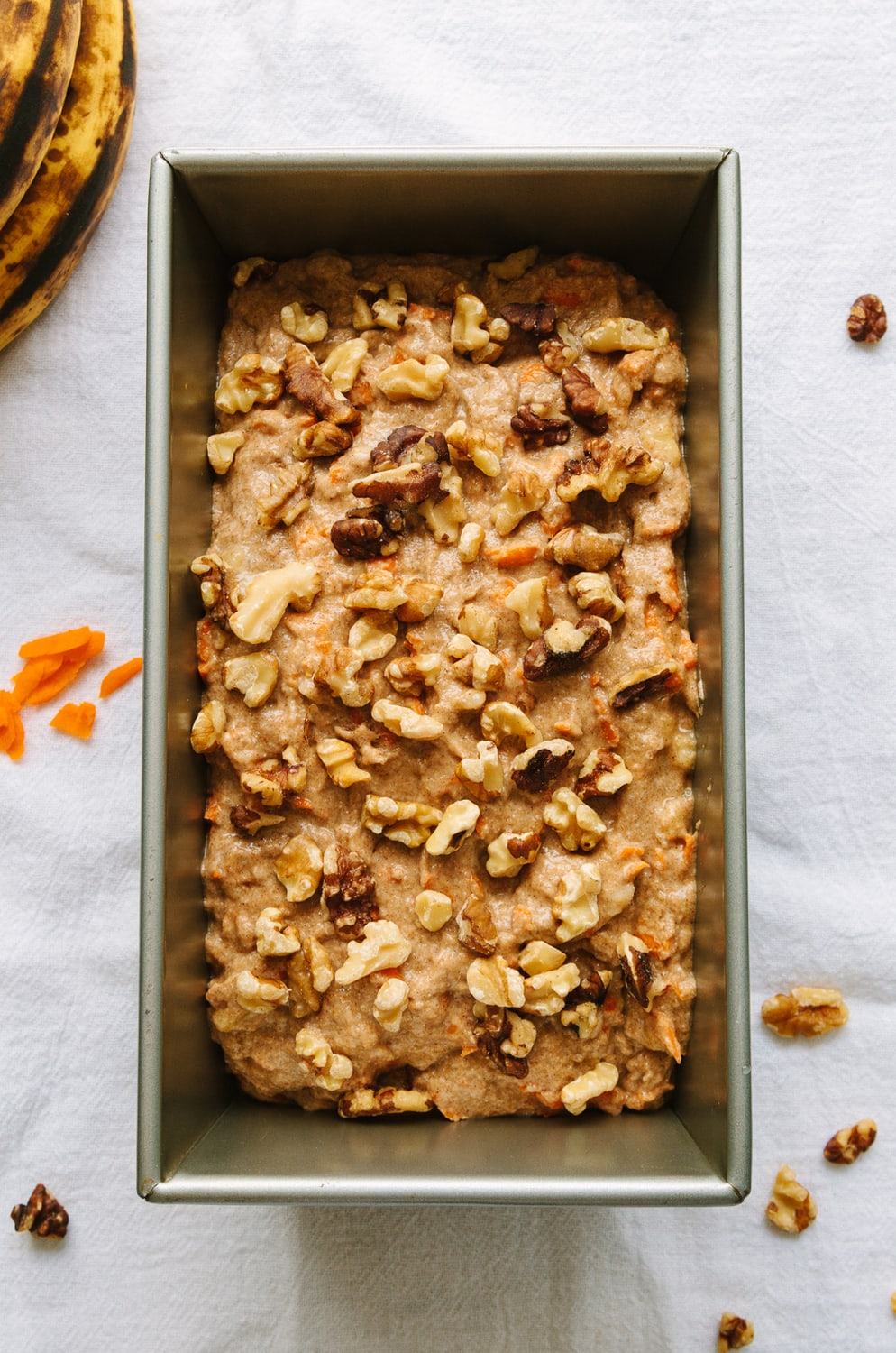 top down view of carrot banana batter added to loaf pan, topped with walnuts and ready for the oven.