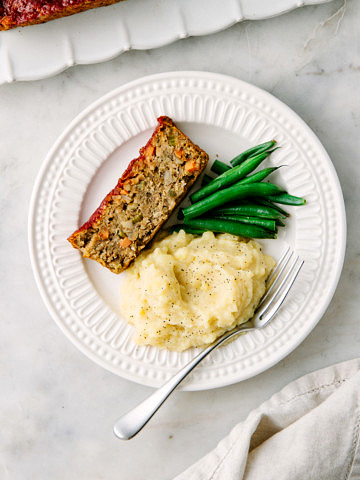 top down view of a serving of vegan lentil loaf with apple, sage and fennel on a white plate with items.