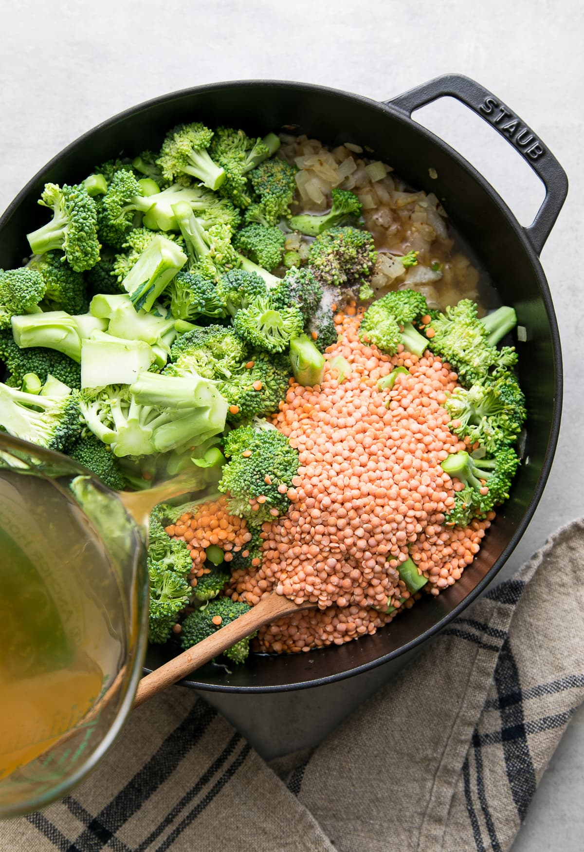 top down view showing the process of adding vegetable broth to pot filled with broccoli red lentil ingredients.
