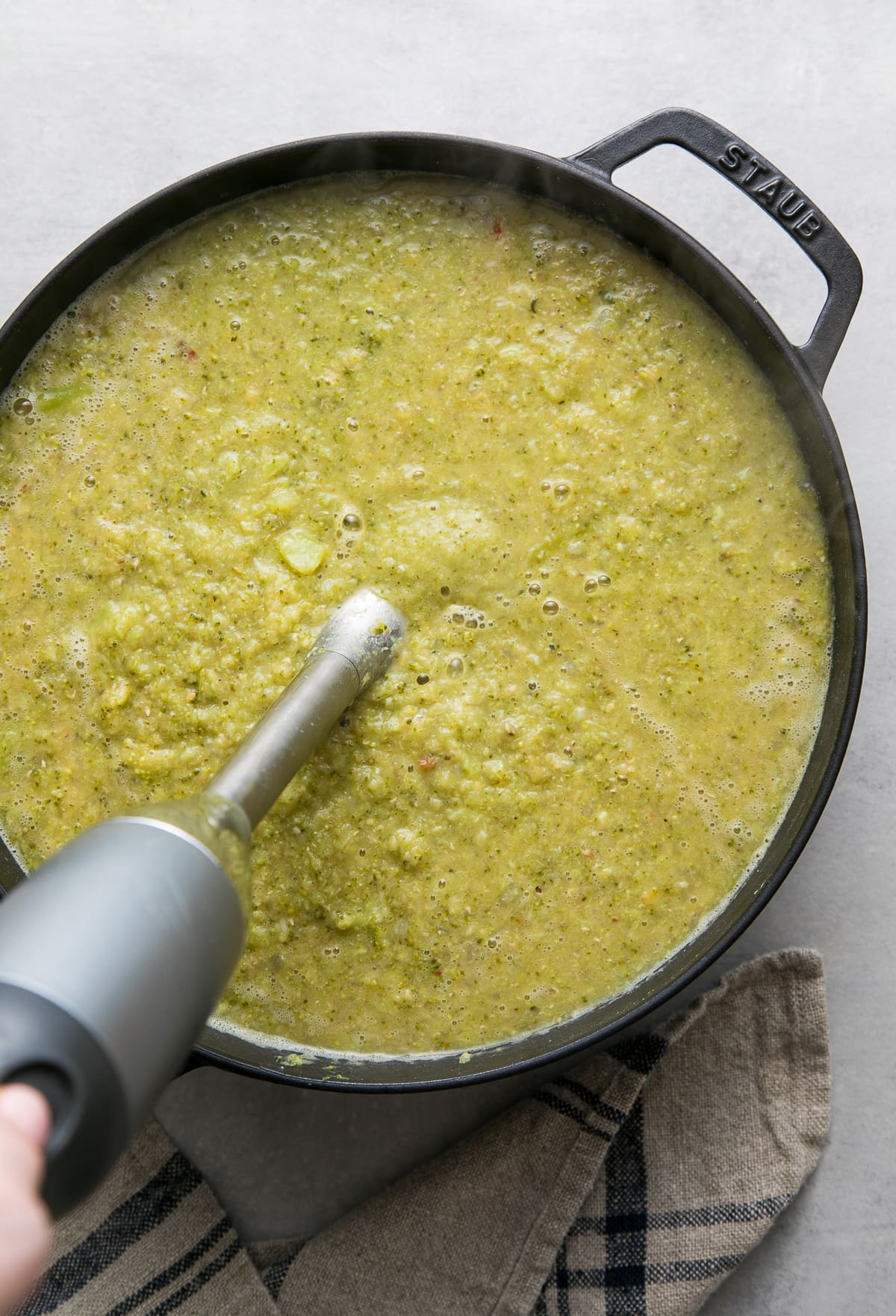top down view showing the process of pureeing creamy broccoli red lentil soup in black pot.
