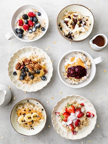 top down view of 6 bowls of healthy oatmeal with various toppings.