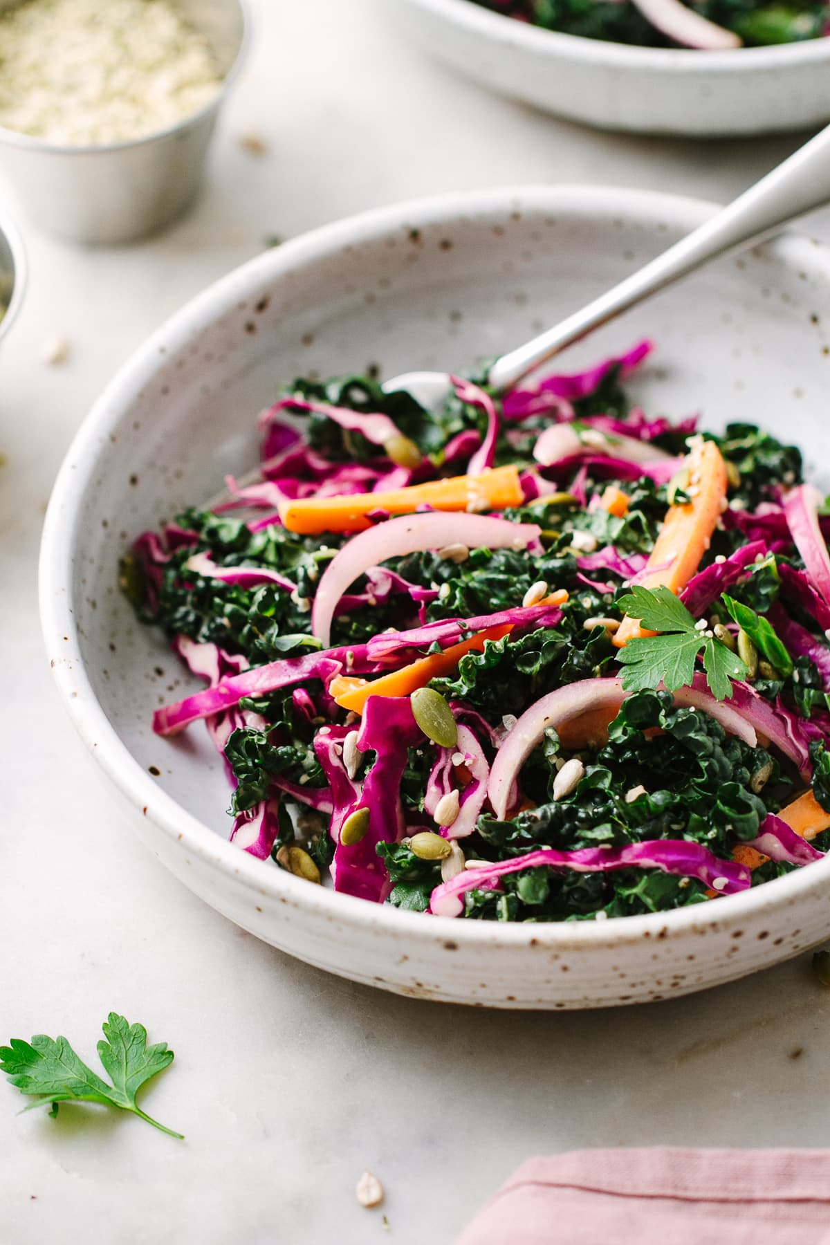 side angle view of bowl with a serving of kale and red cabbage slaw with things surrounded.