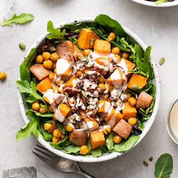 top down view of sweet potato chickpea salad with crispy shallots and tahini dressing with items surrounding.