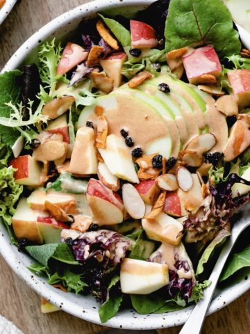 top down view of vegan apple coconut bacon salad with fork and items surrounding.