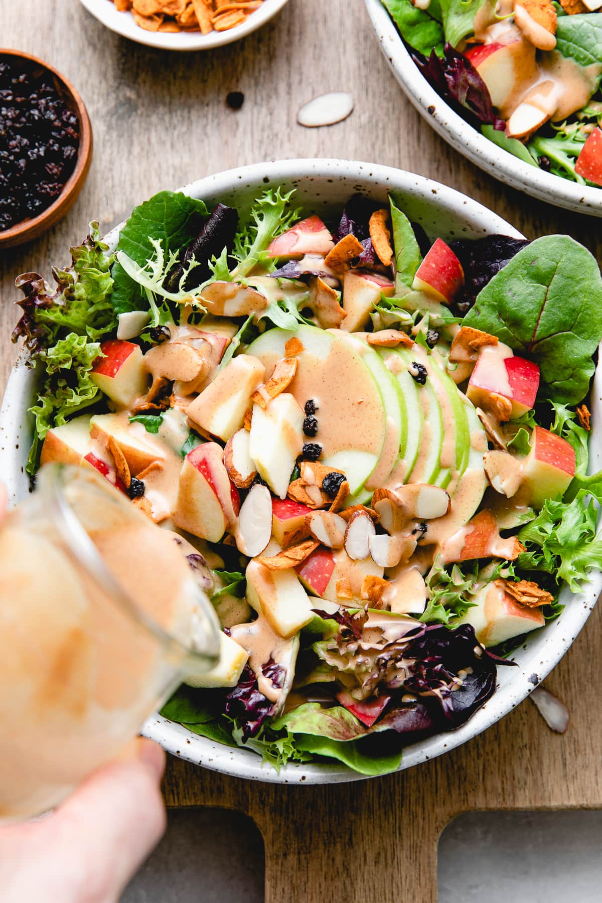 top down view of vegan apple bacon salad being topped with peanut dressing.
