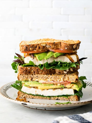 head on view of tofu avocado sandwich sliced in half and stacked on a small plate.
