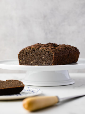 head on view of gluten free buckwheat banana bread on a cake stand with items surrounding.