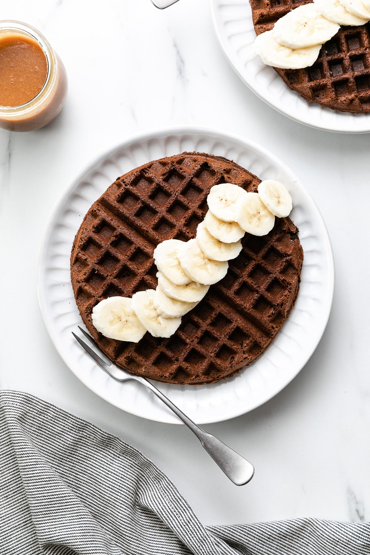 top down view of chocolate buckwheat waffle with items surrounding.