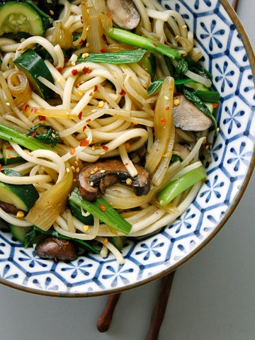 udon noodles with mushrooms and onions in a blue and white bowl