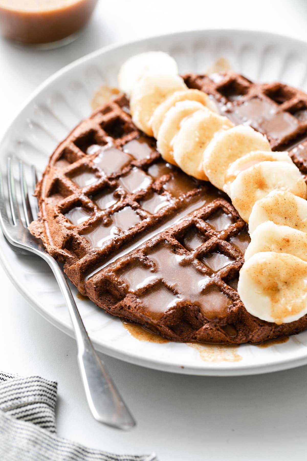 side angle view of chocolate vegan buckwheat waffles with banana and syrup.