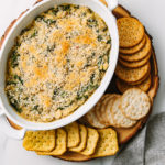 top down view showing the process of adding breadcrumbs to spinach artichoke white bean dip after baking with crackers surrounding.