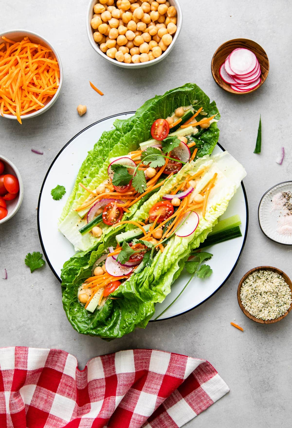 top down view of light and healthy, fresh vegan lettuce wraps on a plate with items surrounding.