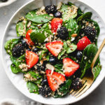 top down view of healthy berry spinach quinoa salad in a bowl.
