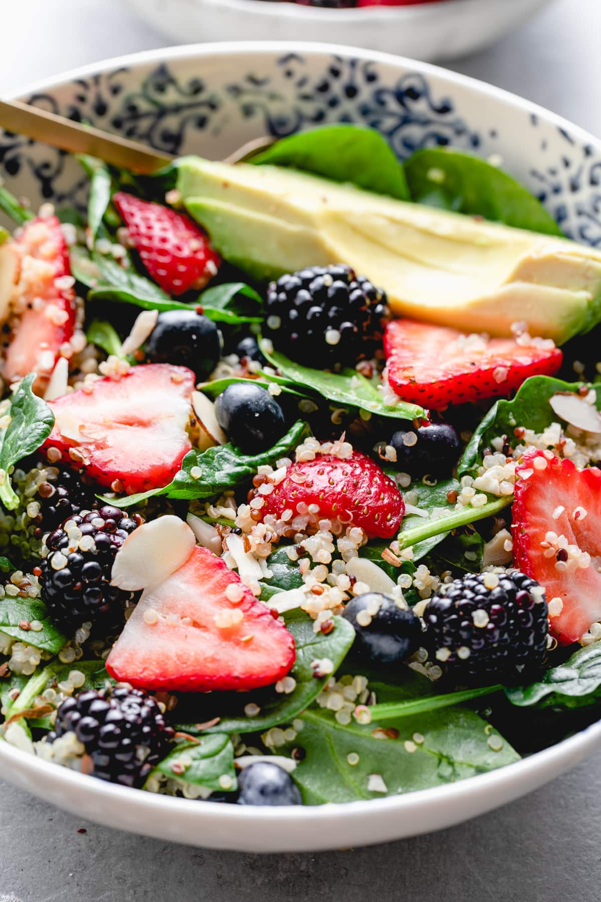 side angle view of healthy berry spinach quinoa salad in a bowl.