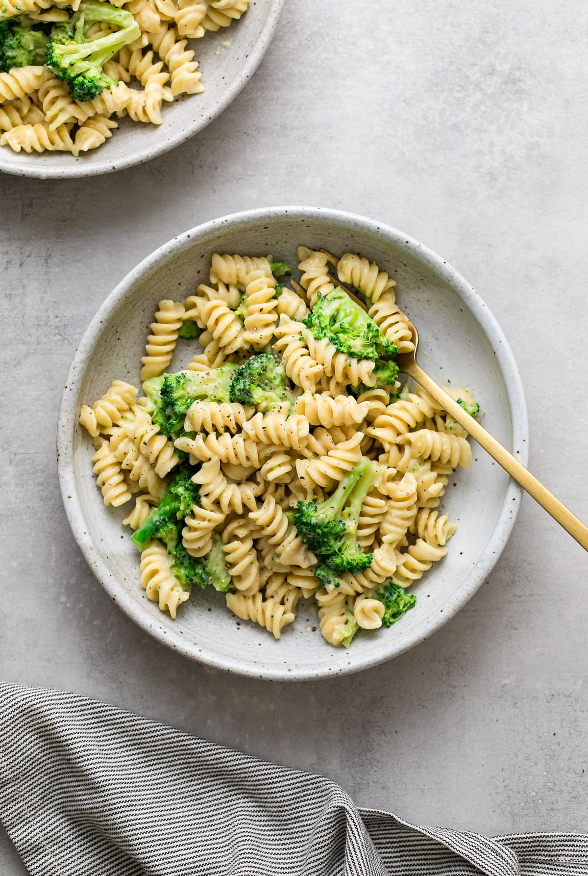top down view of creamy broccoli pasta with gold spoon.