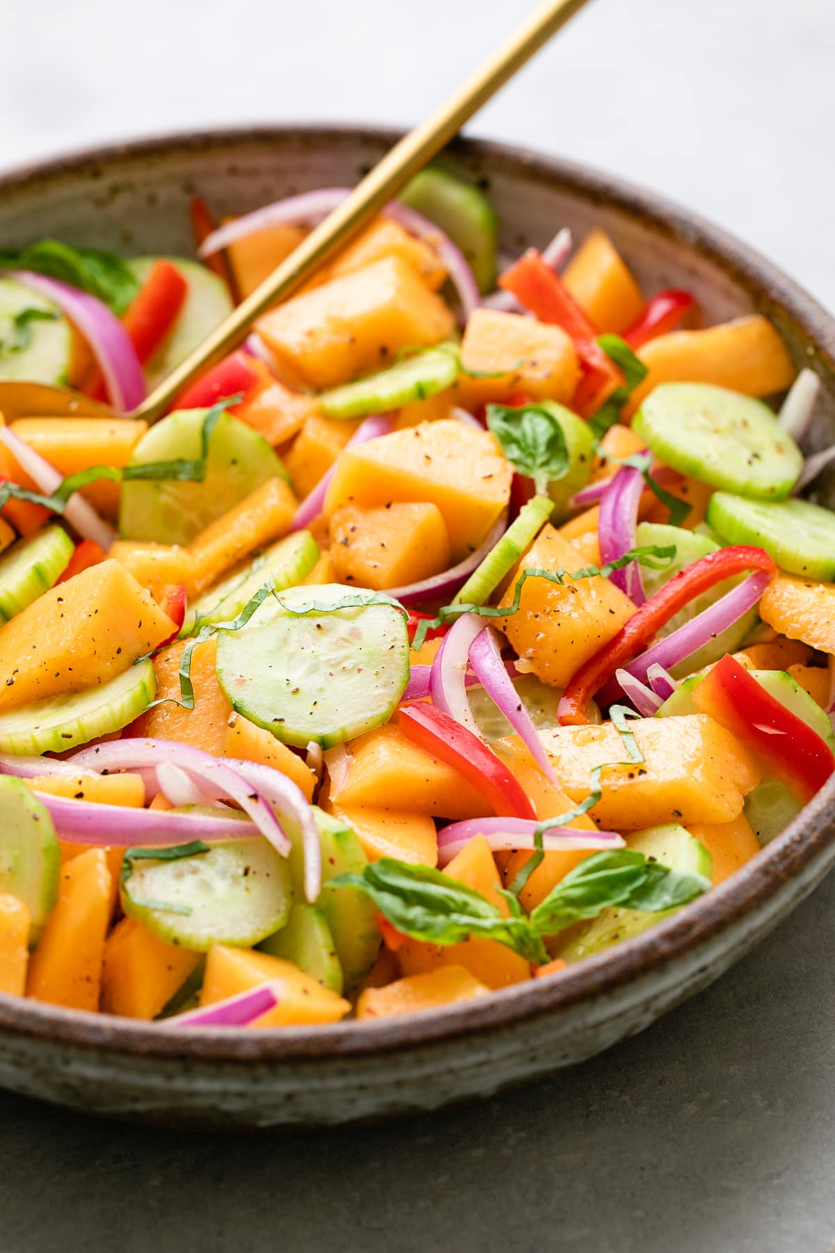 side angle view of cucumber cantaloupe salad in a bowl.