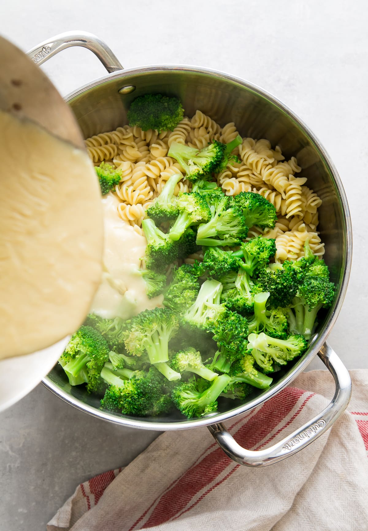 top down view showing the process of pouring creamy vegan sauce into pot of cooked pasta and broccoli.