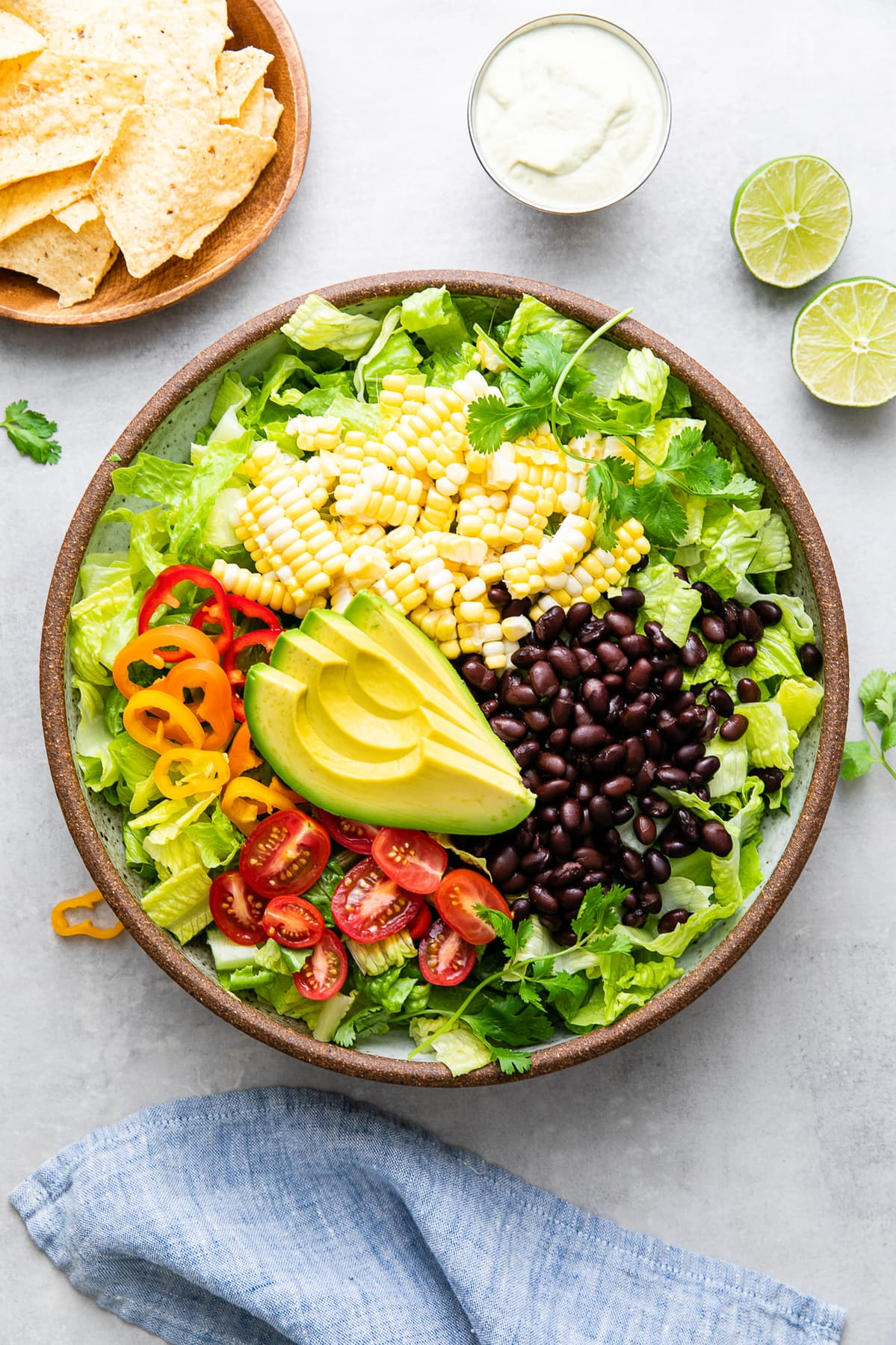 top down view of bowl filled with the ingredients to make vegan southwest salad with items surrounding.