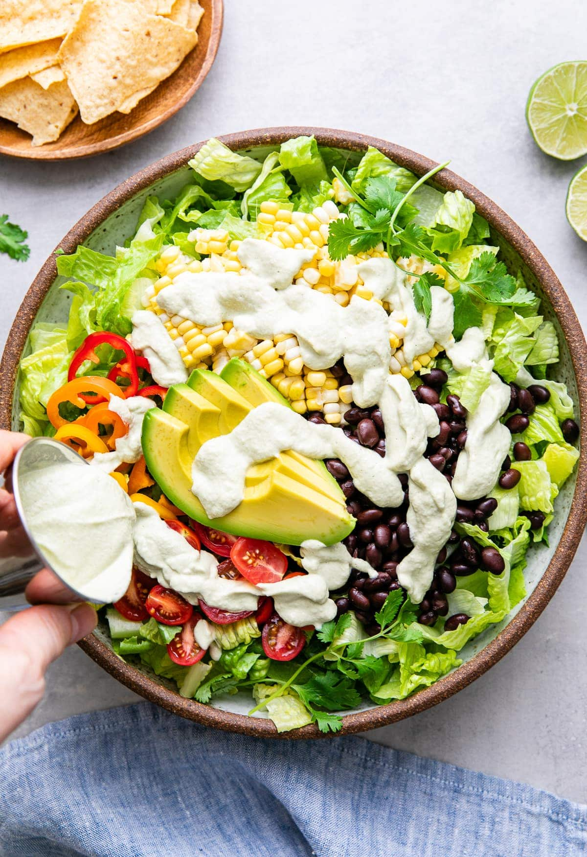 top down view showing creamy hatch ranch dressing being poured over southwestern salad.