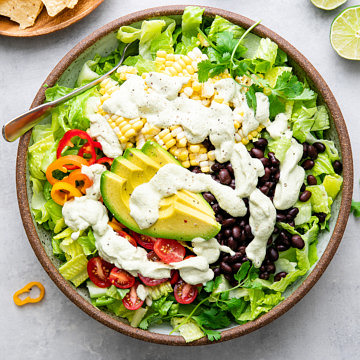 top down view of freshly made southwestern salad in a bowl with items surrounding.