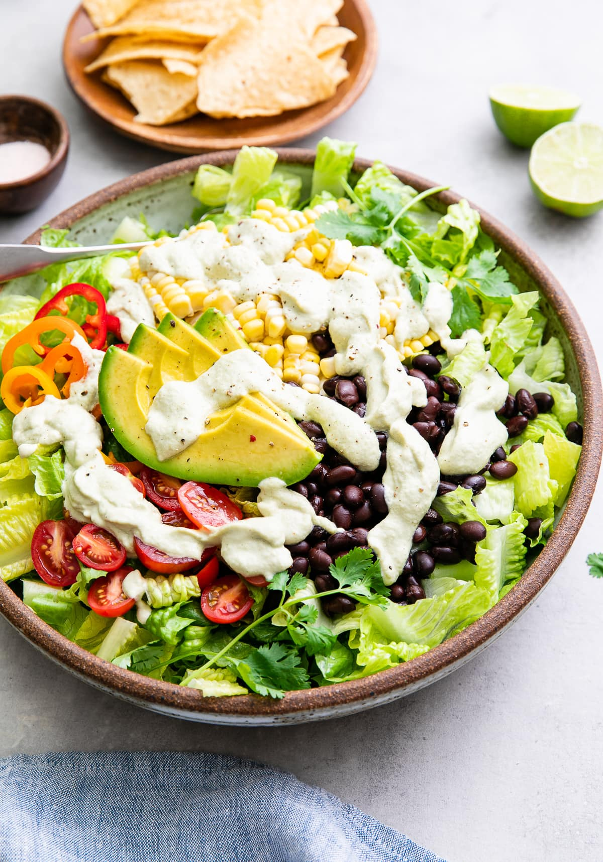 side angle view of freshly made southwestern salad in a bowl with items surrounding.