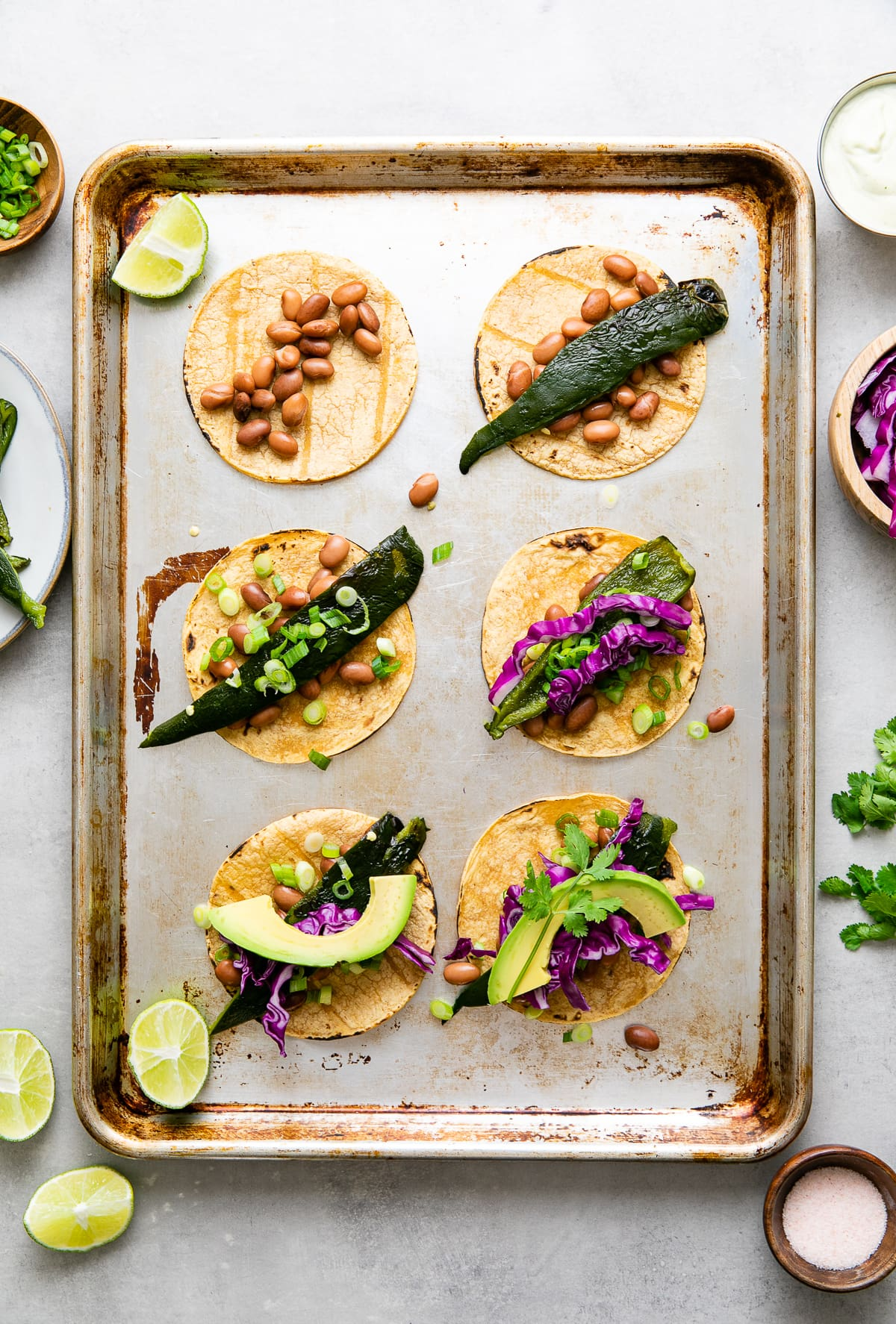 top down view showing the evolution of building poblano tacos on a cookie sheet with items surrounding.