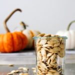 head on view of roasted pumpkin seeds in a glass jar with items surrounding.