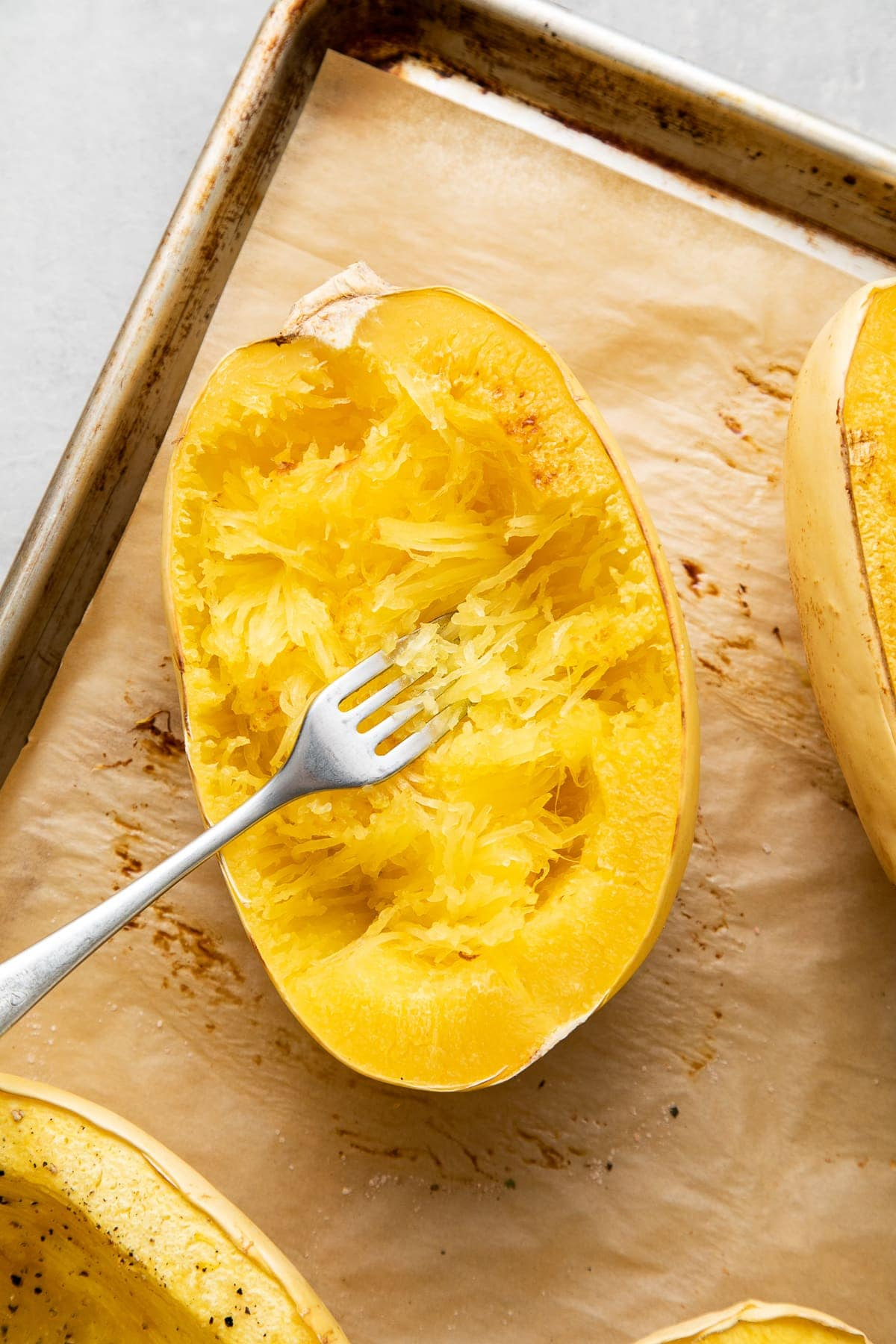top down view showing the process of scraping spaghetti squash from side to side using a fork.
